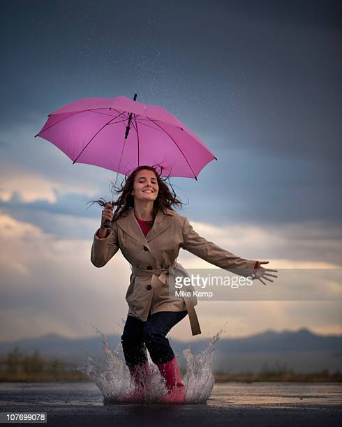 USA, Utah, Lindon, Young woman with umbrella under overcast sky
