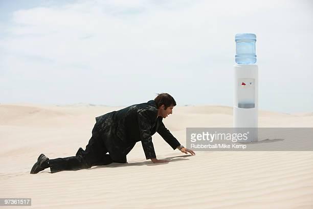USA, Utah, Little Sahara, mid adult businessman crawling to water cooler on desert