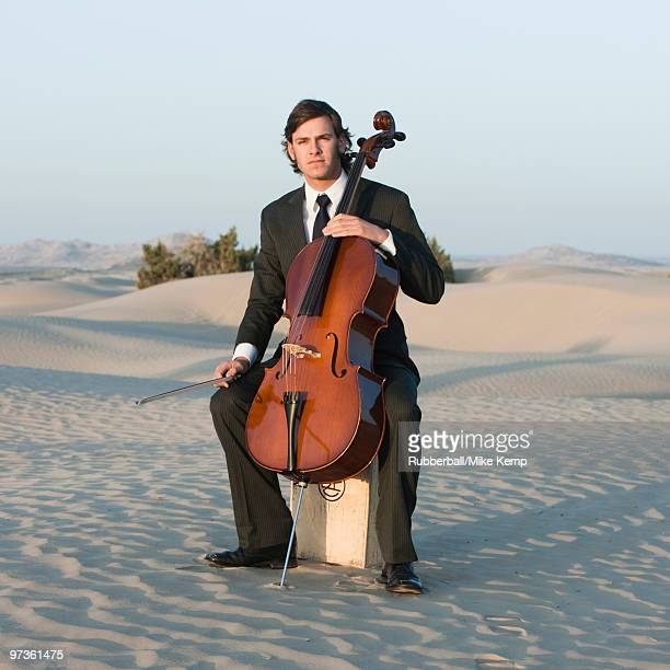 USA, Utah, Little Sahara, portrait of young man with cello in desert