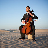 USA, Utah, Little Sahara, young man with cello in desert