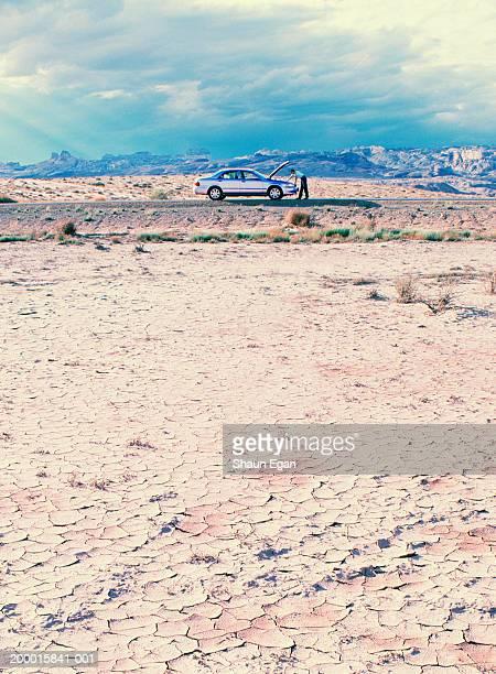 USA, Utah, man looking under bonnet of car in arid landscape