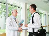 USA, Utah, Ogden, Doctor talking with pharmaceutical representative in hospital corridor
