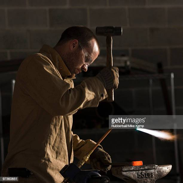 USA, Utah, Orem, man welding with hammer and blowtorch in workshop