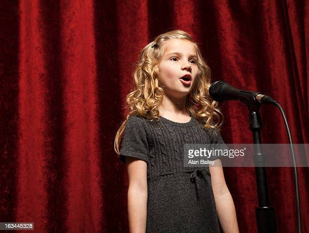 USA, Utah, Orem, Portrait of girl (8-9) singing with microphone