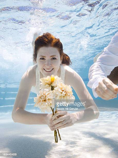 USA, Utah, Orem, Portrait of young woman with bouquet under water