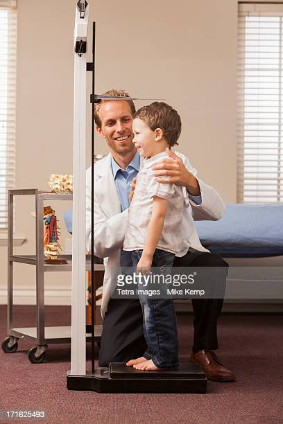 USA, Utah, Provo, Boy (2-3) on scale in doctor's office