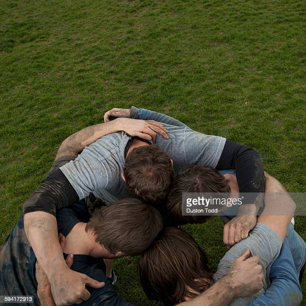USA, Utah, Provo, Friends embracing in football pitch