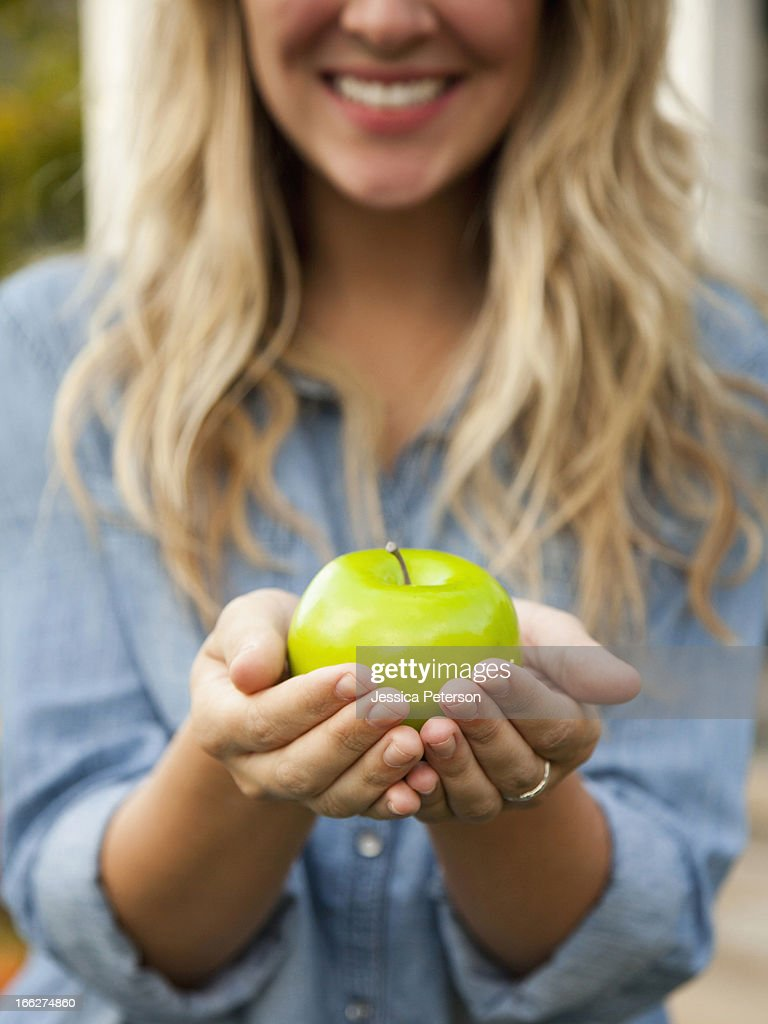USA, Utah, Provo, Mid-section of young woman holding green apple : Stock Photo