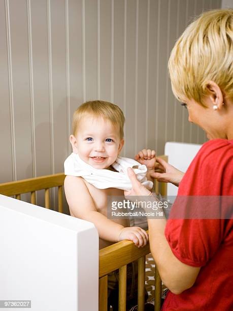 USA, Utah, Provo, Mother dressing baby boy (18-23 months) in crib