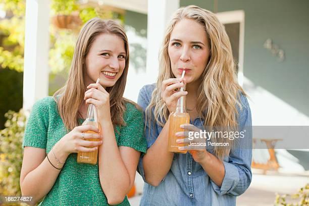 USA, Utah, Provo, Portrait of two friends drinking soda through straw
