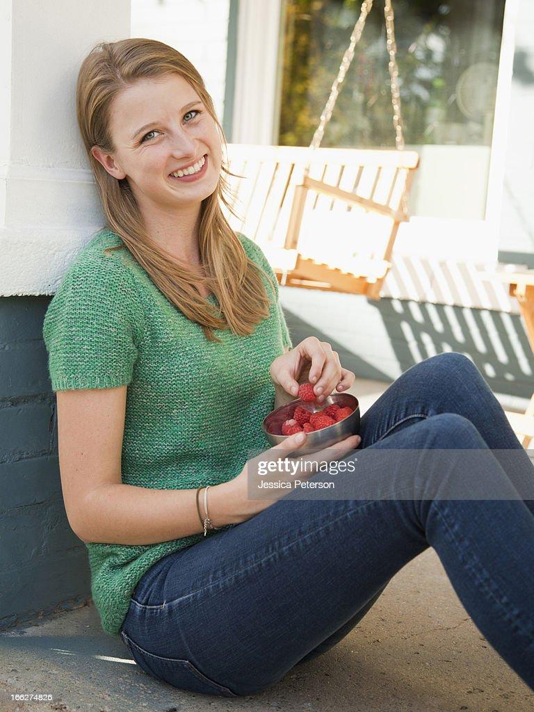 USA, Utah, Provo, Portrait of young woman eating raspberries : Stock Photo
