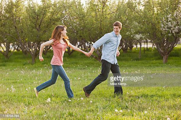USA, Utah, Provo, Young couple running through orchard