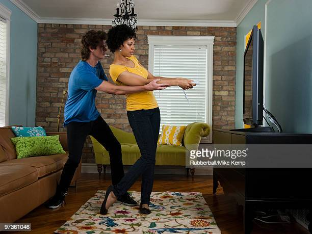 USA, Utah, Provo, young couple using remote control in living room