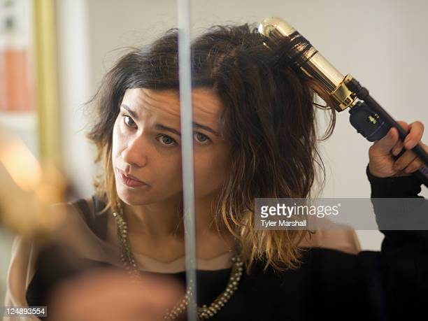 USA, Utah, Provo, Young woman using curler in front of mirror
