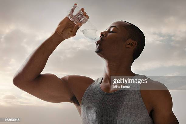 USA, Utah, Salt Lake City, Athlete young man drinking water form bottle, cloudy sky in background