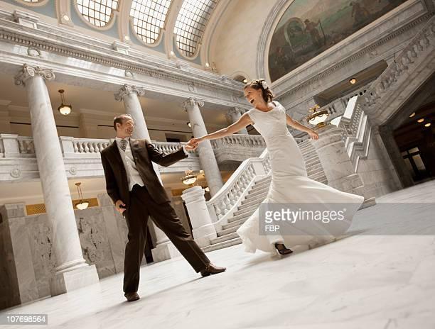 USA, Utah, Salt Lake City, Bride and groom holding hands in mansion