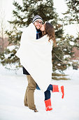USA, Utah, Salt Lake City, Couple wrapped in blanket standing in snow