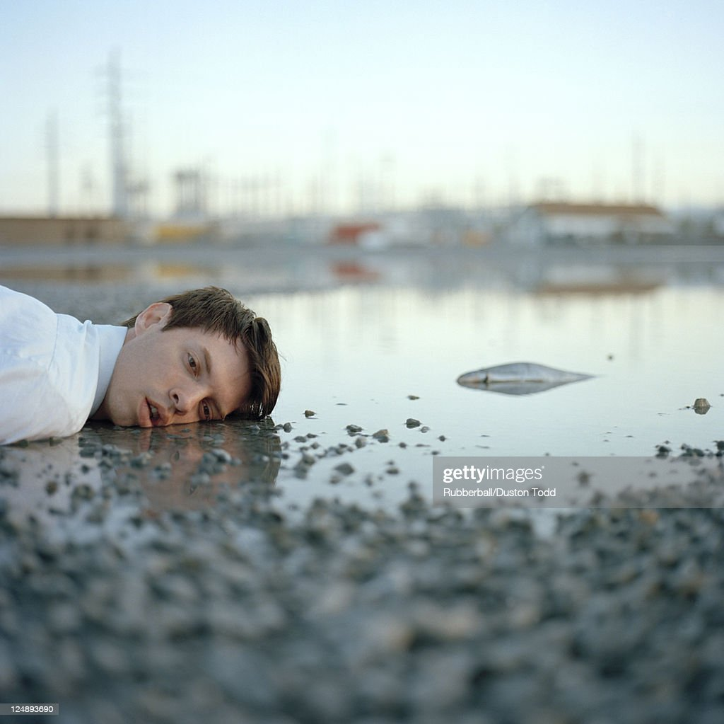 USA, Utah, Salt Lake City, Dead man lying in puddle with dead fish : Stock Photo