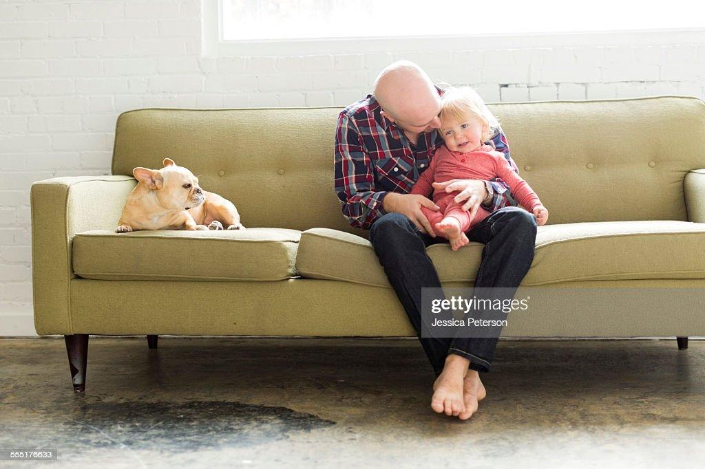 USA, Utah, Salt Lake City, Father sitting on sofa embracing baby son (2-3)
