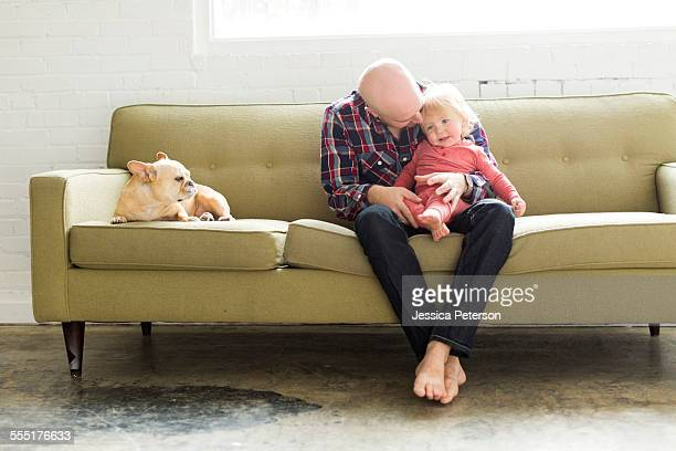USA, Utah, Salt Lake City, Father sitting on sofa embracing baby son (2-3)