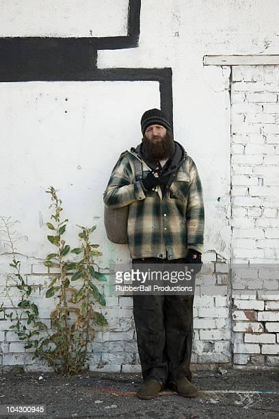 USA, Utah, Salt Lake City, Homeless man standing in front of brick wall