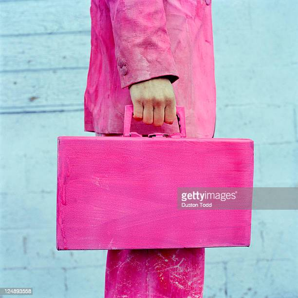 USA, Utah, Salt Lake City, Man in pink suit holding pink briefcase, midsection