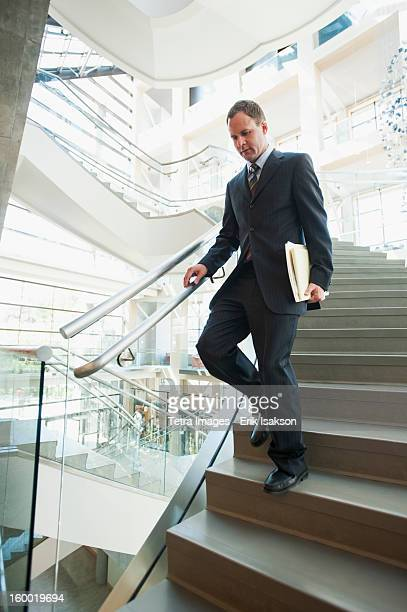 USA, Utah, Salt Lake City, Man walking down stairs in office