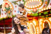 USA, Utah, Salt Lake City, Mother giving her son (4-5 ) piggyback ride in amusement park