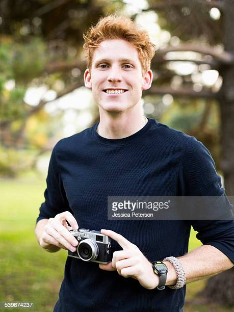 USA, Utah, Salt Lake City, Portrait of young man holding camera in park