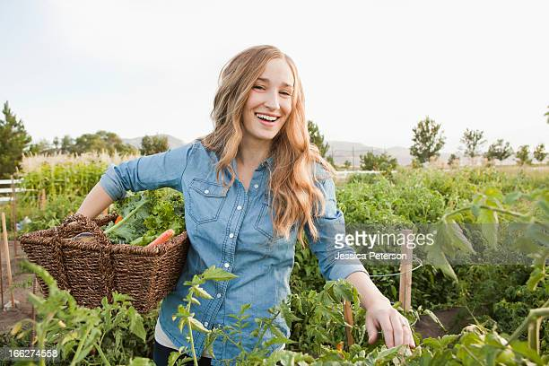 USA, Utah, Salt Lake City, Portrait of young woman harvesting vegetables