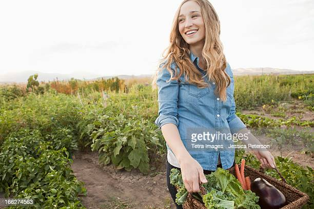 USA, Utah, Salt Lake City, Portrait of young woman harvesting vegetables