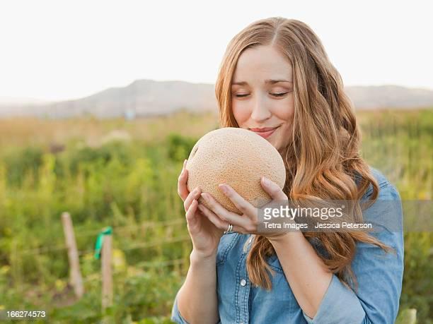 USA, Utah, Salt Lake City, Portrait of young woman holding cantaloupe