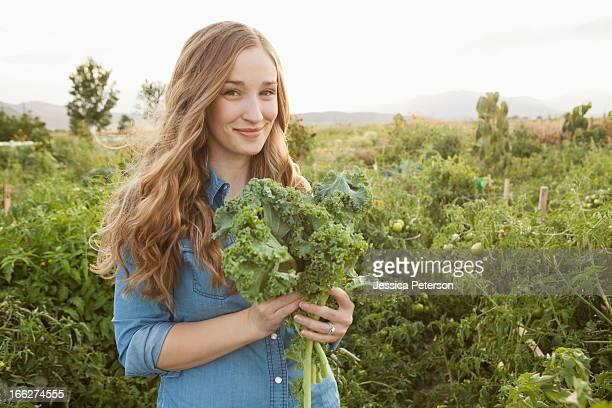 USA, Utah, Salt Lake City, Portrait of young woman holding kale