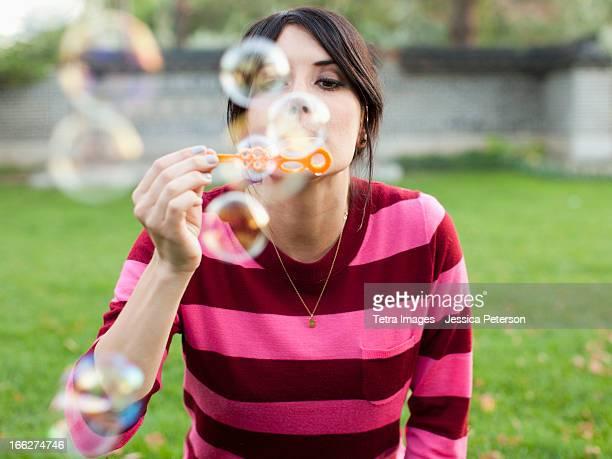 USA, Utah, Salt Lake City, Woman blowing bubbles