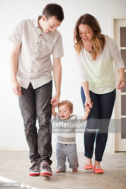 USA, Utah, Salt Lake City, Young couple assisting baby boy (6-11 months) in first steps