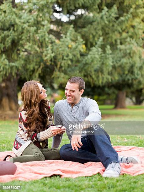 USA, Utah, Salt Lake City, Young couple listening to music in park