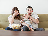 USA, Utah, Salt Lake City, Young couple with baby boy (6-11 months) watching horror film