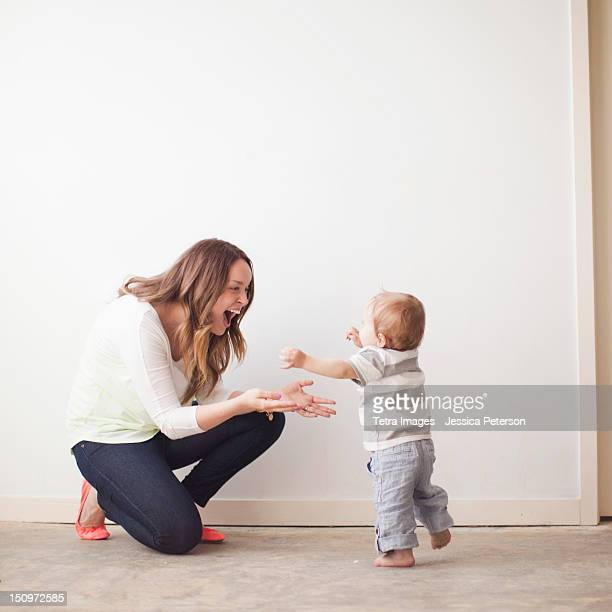 USA, Utah, Salt Lake City, Young mother assisting baby boy (6-11 months) in first steps