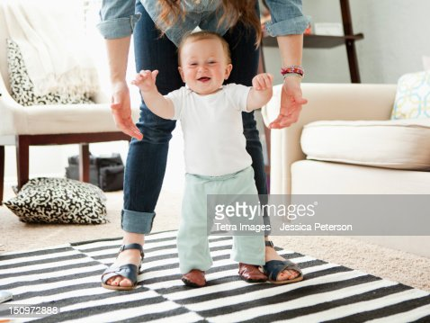USA, Utah, Salt Lake City, Young mother assisting baby boy (6-11 months) in his first steps