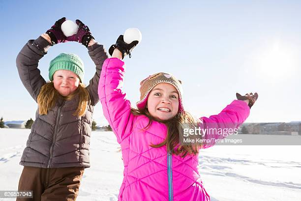 USA, Utah, Saratoga Springs, Girls (8-9, 10-11) playing with snowballs