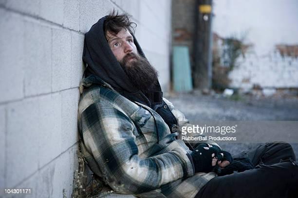 USA, Utah, Satl Lake City, homeless man leanig against wall