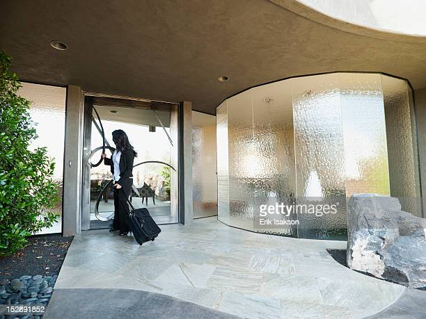USA, Utah, St. George, Woman leaving house with piece of luggage
