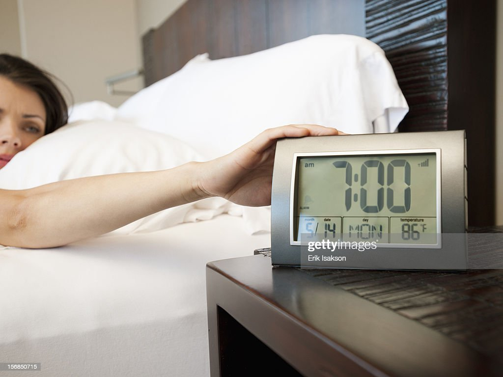 USA, Utah, St. George, Young attractive woman turning off alarm clock