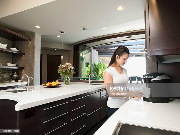 USA, Utah, St. George, Young woman making morning coffee
