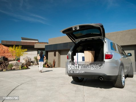 USA, Utah, St. George, Young woman unpacking shopping from car parked in yard