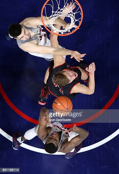 Utah Utes forward Jayce Johnson fights for a rebound with Arizona Wildcats center Dusan Ristic and guard Kadeem Allen during the first half of the...
