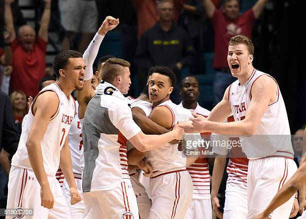 Utah Utes players including Jakob Poeltl celebrate with Lorenzo Bonam of the Utes after he hit a layup at the buzzer to send their semifinal game of...
