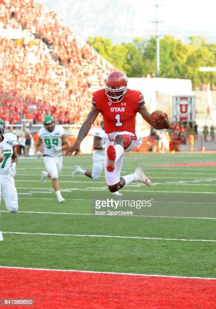 Utah Utes quarterback Tyler Huntley hurdles the goal line for his first touchdown in the first half during a college football game between the North...