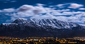 Snow capped Wasatch mountains under a full moon.  Mount Timpanogos can be seen towering over Utah city lights glowing in Lehi, American Fork, Pleasant Grove, and Lindon.  Image captured February 2016.