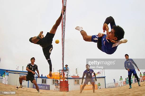 Uthen Kukheaw of Thailand kicks over the net against Mohammad Shukri Jaineh of Brunei Darussalam during the Beach Sepaktakraw Men's Regu Semifinal...